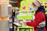 Una mujer se pone unos guantes en un supermercado