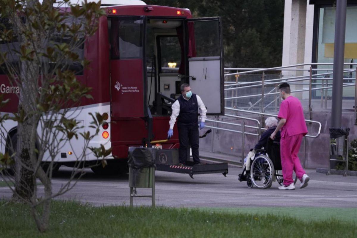 Un enfermero traslada a un anciano residente en Ingurco a un autobús tras ser desalojado por Salud.