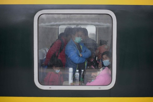 Pasajeros con mascarillas en un tren en Macheng, provincia de Hubei