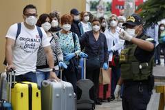 Ciudadanos españoles esperan los autobuses para ser repatriados en Lima.