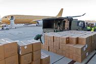 Imagen de las cajas con mascarillas trasladadas desde Tianjin (China) a Getafe (Madrid) por el avión A-330 del fondo.