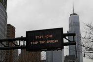 """Un panel de tráfico con el mensaje: """"Permanezca en casa, pare la expansión"""""""