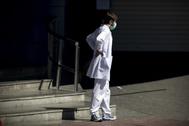 Un miembro del personal sanitario descansa a la puerta de las Urgencias del Hospital Ramon y Cajal.