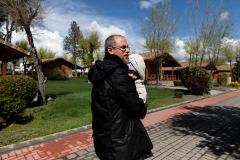 Un hombre con su hija en brazos se dirige al bungalow donde vive, en el Complejo La Cigüeña.