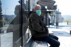 Un hombre con mascarilla espera en una parada de autobús en Orense.