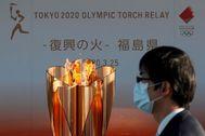 -FOTODELDIA- IWAKI (JAPÓN).- Un hombre con mascarilla pasa junto a la antorcha lt;HIT gt;olímpica lt;/HIT gt; en la localidad de Iwaki, Japón este miércoles tras la decisión del Comité lt;HIT gt;Olímpico lt;/HIT gt; Internacional de aplazar los lt;HIT gt;Juegos lt;/HIT gt; lt;HIT gt;Olímpicos lt;/HIT gt; de Tokio 2020 hasta el año que viene debido al coronavirus.