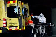 Un técnico sanitario desinfecta una camilla en el Hospital de Bellvitge.