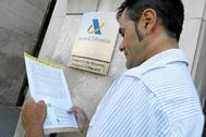 Un hombre sujeta el borrador de su declaración de la renta