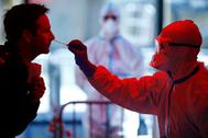 Un sanitario toma muestras en un centro para realizar test en Colonia.
