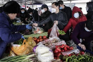 Gente comprando con mascarillas en un mercado de Wuhan a finales de enero.
