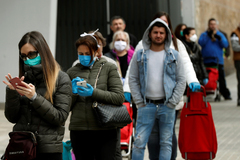 Varias personas hacen cola en un supermercado de Madrid durante el estado de alarma.