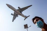 Un hombre con mascarilla camina mientras un avión de Qatar aterriza en el aeropuerto de Katmandú.