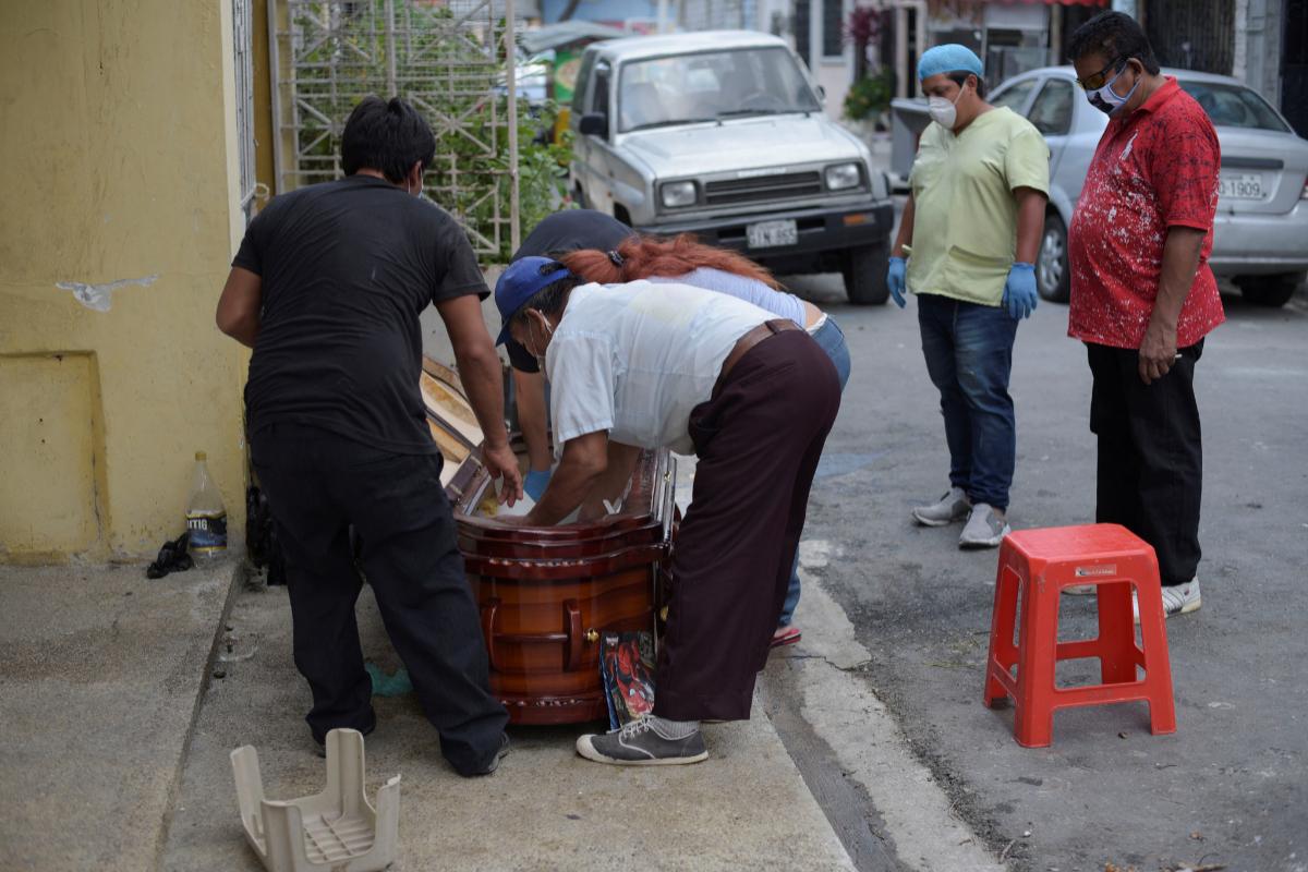 Familiares acomodan en el ataúd el cuerpo de una mujer fallecida, en Guayaquil.