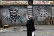 Un hombre con mascarilla pasea en un mercado de Jerusalén.