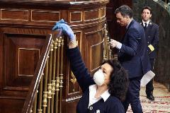 Pedro Sánchez accediendo a la tribuna del Congreso el 18 de marzo mientras una trabajadora desinfecta la barandilla.
