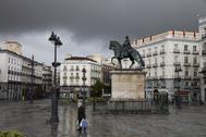 Una mujer camina por la Puerta del Sol de Madrid, desierta por el confinamiento decretado por el Estado de Alarma debido al coronavirus.