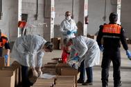 Personal sanitario de Castellón revisa unas cajas que contienen material de protección sanitario.
