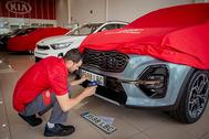 Un operario preparando la entrega de un vehículo nuevo.
