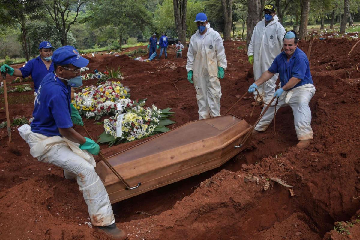 Sepultureros realizan un entierro en el cementerio de Vila Formosa.