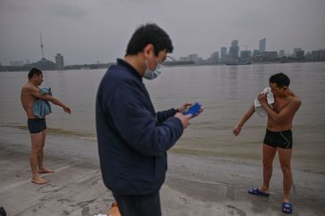 TOPSHOT - Men dry their bodies after swimming in Yangtze River in lt;HIT gt;Wuhan lt;/HIT gt;, on April 2, 2020. - lt;HIT gt;Wuhan lt;/HIT gt;, the central Chinese city where the coronavirus first emerged last year, partly reopened on March 28 after more than two months of near total isolation for its population of 11 million. (Photo by Hector RETAMAL / AFP)