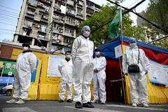 Sanitarios chinos guardan tres minutos de silencio en las calles de Wuhan.