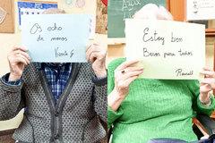 Dos residentes muestran carteles para sus familias para transmitirles que están bien.