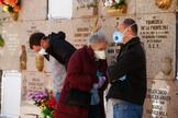 Una familia llora la muerte de un familiar en un cementerio de Madrid.