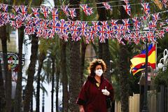 Una única transeunte con mascarilla pasea por la denominada 'zona inglesa' de Benidorm, normalmente atestada de gente en esta época del año.