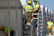 Un grupo de bomberos trabaja, ayer, en la instalación del hospital de campaña.