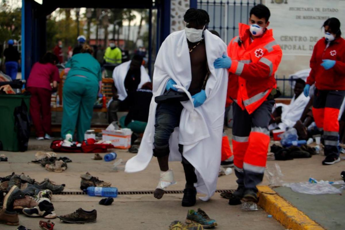 Un miembro de la Cruz Roja traslada a un inmigrante herido durante el salto.
