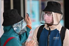 Una pareja con la cara cubierta para protegerse del Covid-19, habla, en Wuhan.