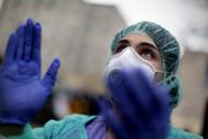 Una trabajadora sanitaria aplaude en el hospital Gregorio Marañón ataviada con su Equipo de Protección Individual.