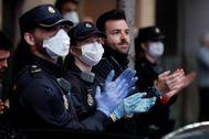 Agentes de la Policía Nacional aplauden el trabajo de los sanitarios en el Hospital de la Princesa de Madrid.