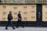 London (United Kingdom).- Armed police walk past a boarded up pub in London, Britain, 08 April 2020. According to news reports, new ways of boarding London's buses are being looked at to reduce contact for drivers during the coronavirus pandemic. Nine bus workers have now died in the UK from Covid-19, Transport for London (TfL) is calling for passengers to board buses using the middle door to reduce passengers' contact with drivers. ( lt;HIT gt;Reino lt;/HIT gt; lt;HIT gt;Unido lt;/HIT gt;, Londres) EPA/