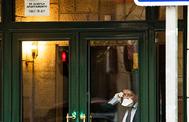 Un hombre con mascarilla dentro de un portal con cartel de 'Se alquila'.