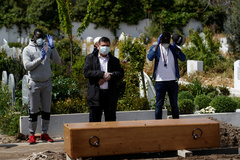 People wearing protective face masks pray in front of the lt;HIT gt;coffin lt;/HIT gt; of a person who died of lt;HIT gt;coronavirus lt;/HIT gt; disease (COVID-19), at the Spanish muslim military cemetery, in Grinon