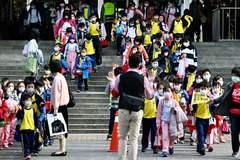 Los niños con mascarillas abandonan su escuela primaria al final del día en el distrito de Xindian, Nueva Ciudad de Taipei.