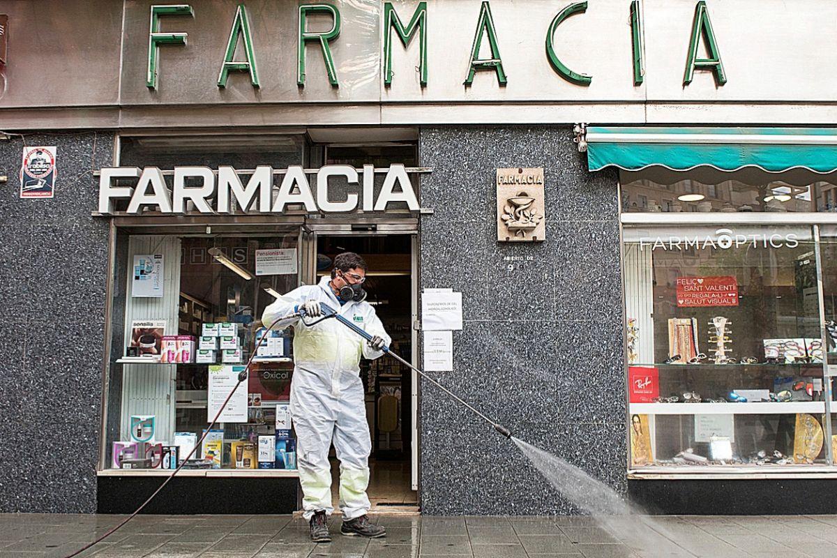 Un operario de Emaya desinfecta el exterior de una farmacia en la calle San Miguel. ALBERTO VERA