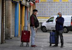 Dos hombres con mascarilla hablan manteniendo la distancia en la puerta de un mercado de Valencia.