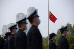 Policías chinos, en una ceremonia en homenaje a las víctimas del coronavirus en Wuhan.