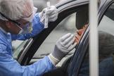 Un sanitario realiza una prueba a una mujer para detectar si tiene coronavirus.
