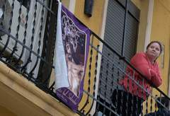 A woman stands on her balcony, adorned with imagery to celebrate Easter, on April 9, 2020, in El Cabanal, in lt;HIT gt;Valencia lt;/HIT gt;, after religious processions were cancelled during a national lockdown to prevent the spread of the COVID-16 disease. - In the week leading up to Easter Sunday, hundreds of colourful processions featuring penitents in cone-shaped hoods and centuries-old religious floats traditionally flood the streets of villages and cities across Spain. But with a nationwide lockdown in place to curb the spread of the lt;HIT gt;coronavirus lt;/HIT gt;, Spaniards this year are finding ways to mark Holy Week from their homes, by blasting religious music from their balconies or viewing videos of last year's parades. (Photo by JOSE JORDAN / AFP)