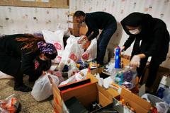 Voluntarios de la Sociedad Imam Ali, una ONG iraní de asistencia a los pobres, recopilan alimentos y productos higiénicos para los vecinos del barrio de Jac Sefid, en el este de Teherán.