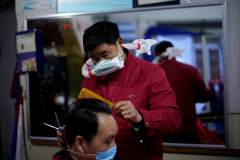 Yang Guangyu, 54, a local barber working in his shop at a blocked residential area, wears his handmade mask assembled from a water bottle, mask and a plastic pipe, as he works after the lockdown was lifted in lt;HIT gt;Wuhan lt;/HIT gt;