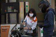 Una empleada de una gasolinera vizcaína sirve carburante a una motocicleta protegida con una mascarilla.