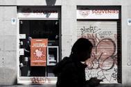 Una persona pasa frente a un comercio cerrado en el centro de Madrid la semana pasada.