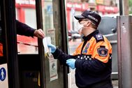 Un voluntario entrega una de las mascarillas higiénicas a un usuario de un autobús en Almería.