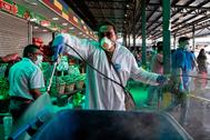 Un trabajador del servicio de limpieza realiza labores de desinfección en el mercado central de Santiago.