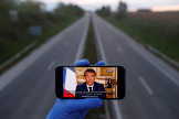 A mobile phone showing French President Emmanuel lt;HIT gt;Macron lt;/HIT gt;, as he addresses the nation about the coronavirus disease (COVID-19) outbreak is displayed for a phot in front of an almost empty motorway in Strasbourg
