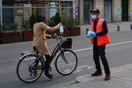 Un voluntario de Cruz Roja entrega una mascarilla a una ciclista en el centro de Vitoria.